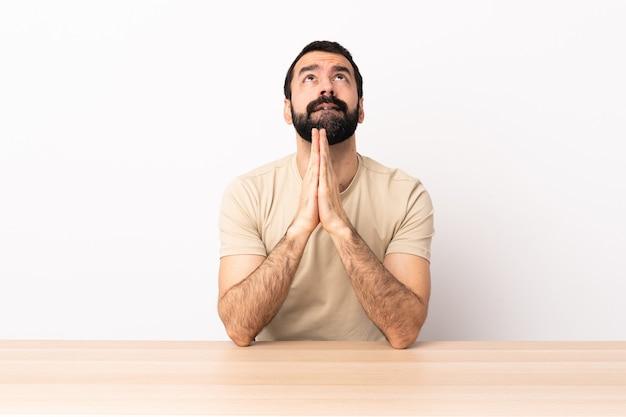 Homem caucasiano com barba em uma mesa mantém as palmas das mãos juntas. a pessoa pede algo.