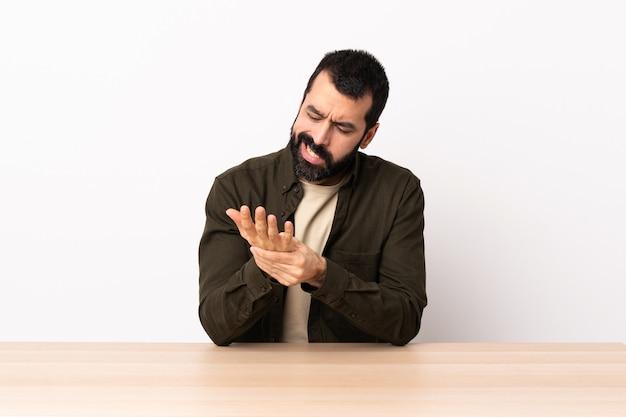 Homem caucasiano com barba em uma mesa que sofre de dor nas mãos