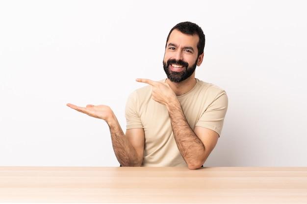 Homem caucasiano com barba em uma mesa segurando copyspace imaginário na palma da mão para inserir um anúncio.