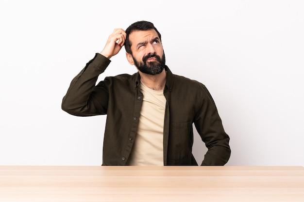 Homem caucasiano com barba em uma mesa, tendo dúvidas enquanto coça a cabeça.
