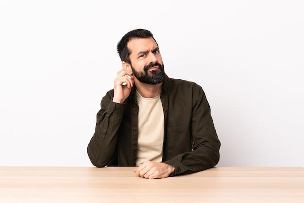 Homem caucasiano com barba em uma mesa, tendo dúvidas.