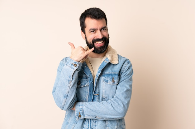 Homem caucasiano com barba mais isolado fazendo gesto de telefone. ligue para mim de volta
