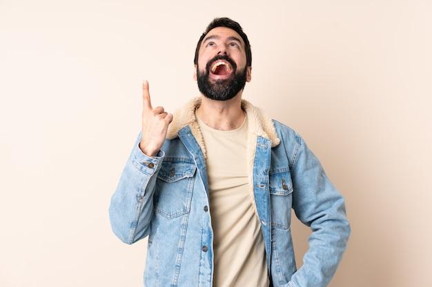 Homem caucasiano com barba no isolado apontando para cima e surpreso