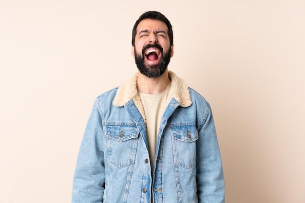 Homem caucasiano, com barba, parede, gritando, frente, boca aberta