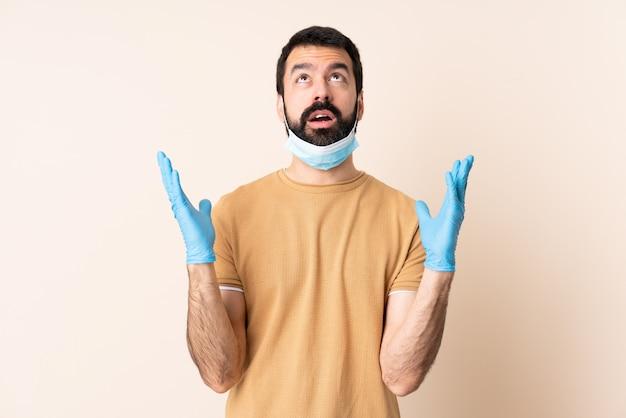 Homem caucasiano, com barba, protegendo com uma máscara e luvas sobre parede estressado oprimido