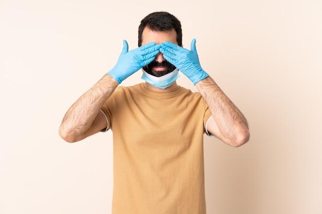 Homem caucasiano com barba, protegendo com uma máscara e luvas sobre parede isolada, cobrindo os olhos pelas mãos e sorrindo