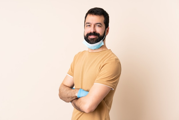 Homem caucasiano com barba, protegendo com uma máscara e luvas sobre parede isolada com os braços cruzados e olhando para a frente