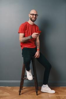 Homem caucasiano com barba, segurando um telefone no braço enquanto sorrindo em fundo cinza studio