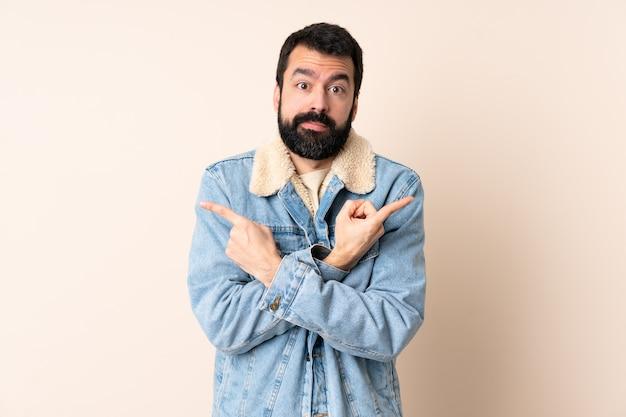 Homem caucasiano com barba sobre parede isolada apontando para as laterais tendo dúvidas
