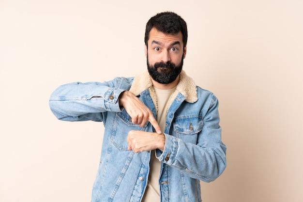 Homem caucasiano com barba sobre parede isolada fazendo o gesto de estar atrasado