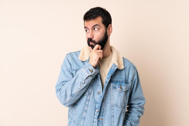 Homem caucasiano com barba sobre parede isolada, tendo dúvidas e com a expressão do rosto confuso