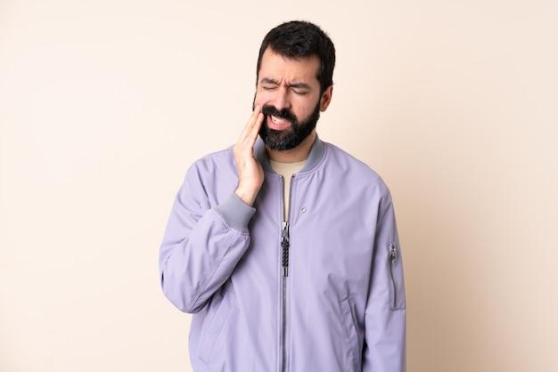 Homem caucasiano com barba, vestindo um casaco por cima da parede com dor de dente