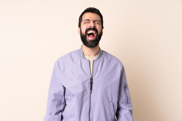 Homem caucasiano com barba, vestindo um casaco por cima da parede, gritando para a frente com a boca aberta