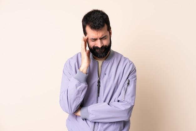 Homem caucasiano com barba, vestindo um casaco por cima do muro com dor de cabeça