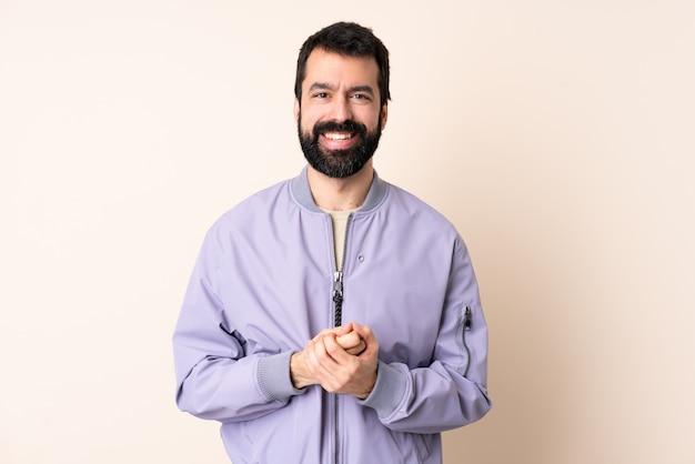 Homem caucasiano com barba, vestindo uma jaqueta na risada isolada