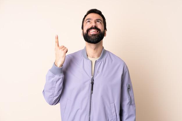 Homem caucasiano com barba, vestindo uma jaqueta no isolado apontando para cima e surpreso
