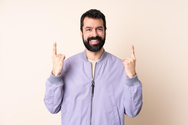 Homem caucasiano com barba vestindo uma jaqueta sobre fundo isolado apontando para uma ótima ideia