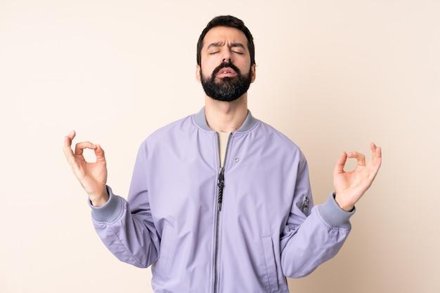 Homem caucasiano com barba, vestindo uma jaqueta sobre isolado em pose de zen