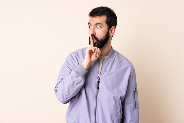 Homem caucasiano com barba, vestindo uma jaqueta sobre isolado mostrando um sinal de gesto de silêncio colocando o dedo na boca