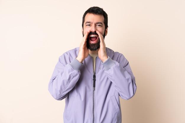 Homem caucasiano com barba, vestindo uma jaqueta sobre parede isolada, gritando e anunciando algo