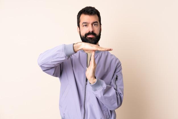 Homem caucasiano com barba vestindo uma jaqueta sobre um fundo isolado fazendo gesto de castigo
