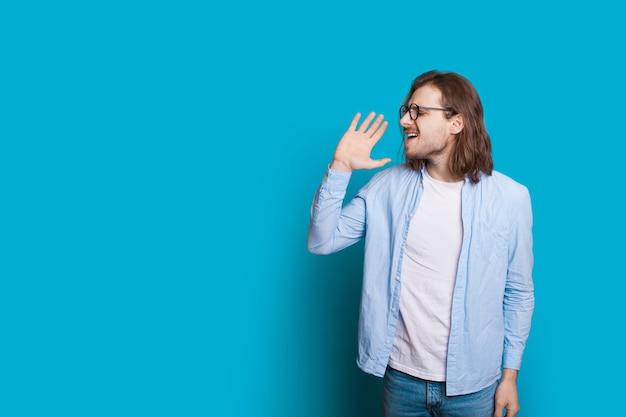 Homem caucasiano com cabelo comprido e barba cantando e posando em uma parede azul com espaço livre