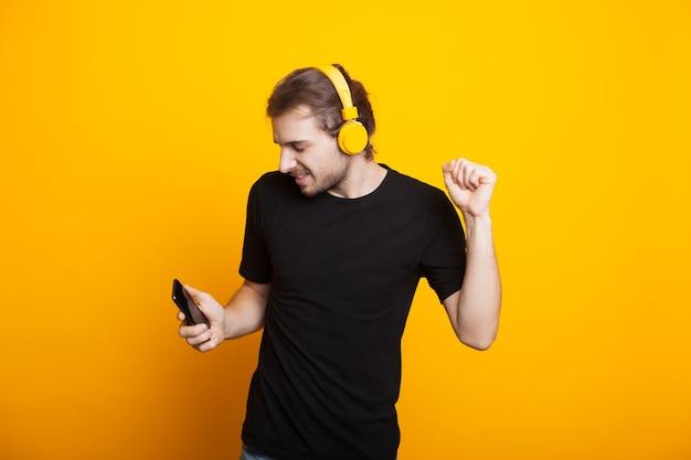 Homem caucasiano com cabelo comprido e barba dançando com fones de ouvido na parede amarela segurando o telefone