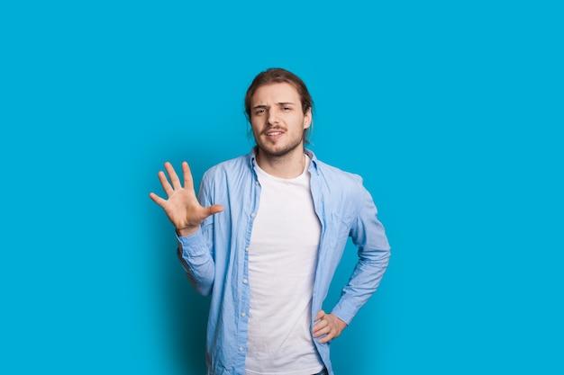 Homem caucasiano com cabelo comprido e barba gesticulando com a palma da mão número 5 enquanto posa em uma parede azul do estúdio