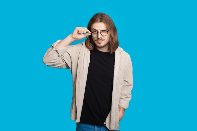Homem caucasiano com cabelo comprido tocando seus óculos e olhando para a câmera em uma parede azul