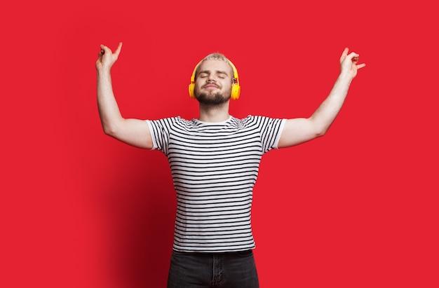 Homem caucasiano com cabelo loiro, ouvindo música em fones de ouvido e gesticulando com o cartaz de rock and roll na parede vermelha do estúdio