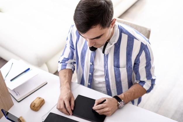 Homem caucasiano com camisa azul desenha em tablet gráfico, trabalho remoto, designer gráfico, conceito freelancer