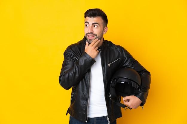 Homem caucasiano com capacete de motocicleta em amarelo isolado, olhando para cima enquanto sorri