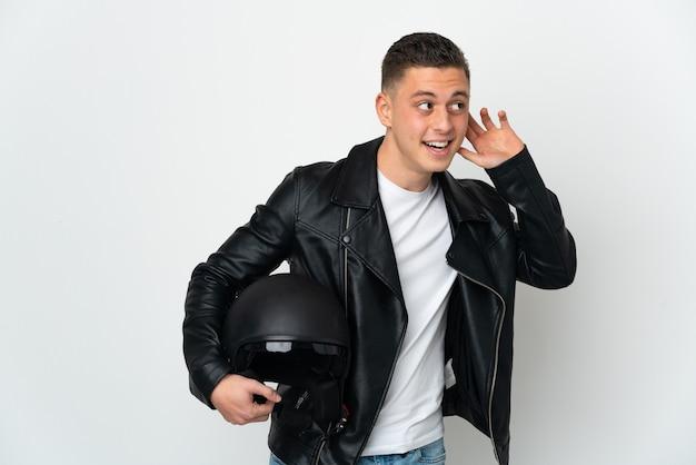 Homem caucasiano com capacete de motociclista isolado na parede branca, ouvindo algo colocando a mão na orelha