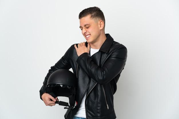 Homem caucasiano com capacete de motociclista isolado no fundo branco, sofrendo de dores no ombro por ter feito esforço