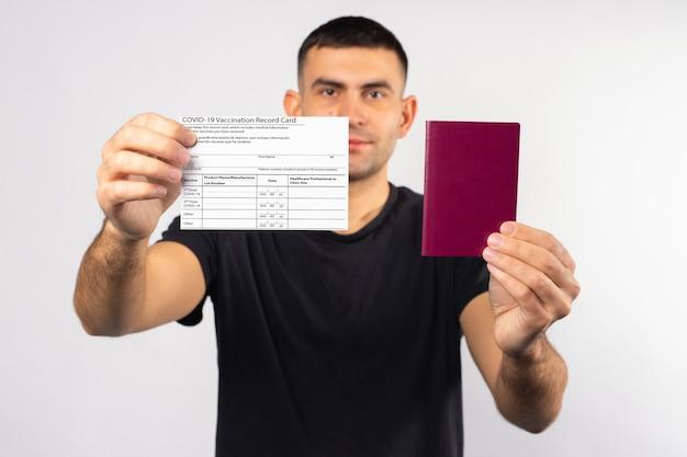 Homem caucasiano com cartão de vacinação e passaporte nas mãos o conceito de condições para voar