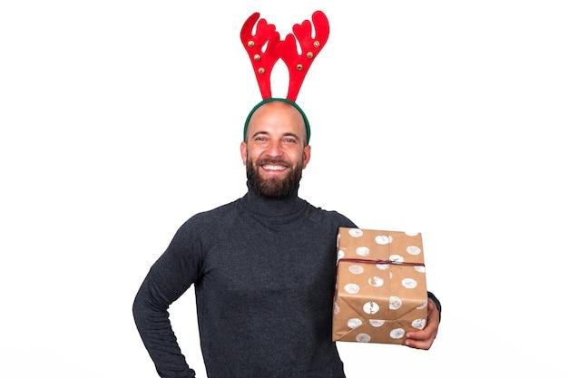Homem caucasiano com chifres de rena olhando para a câmera segurando um presente de natal.