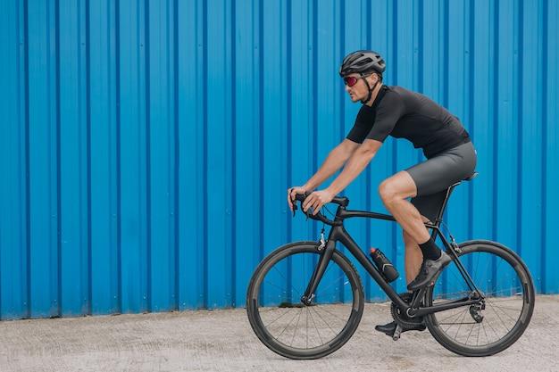 Homem caucasiano com corpo musculoso andando de bicicleta na parede azul