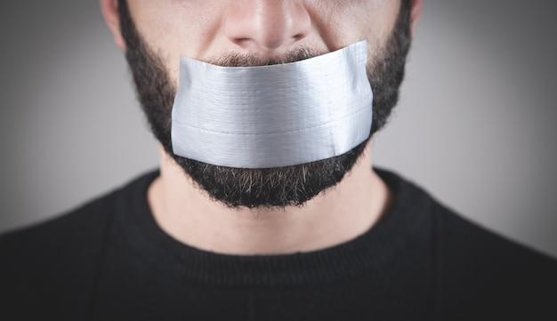Homem caucasiano com fita adesiva na boca. censura