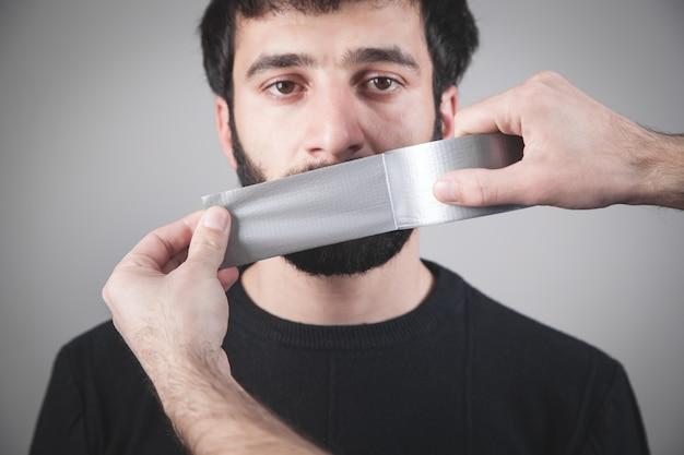 Homem caucasiano com fita adesiva na boca.