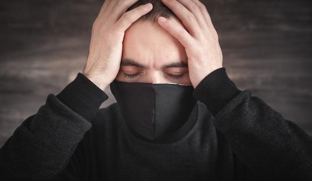 Homem caucasiano com máscara facial preta.