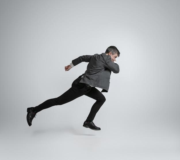 Homem caucasiano com roupa de escritório correndo isolado na parede cinza