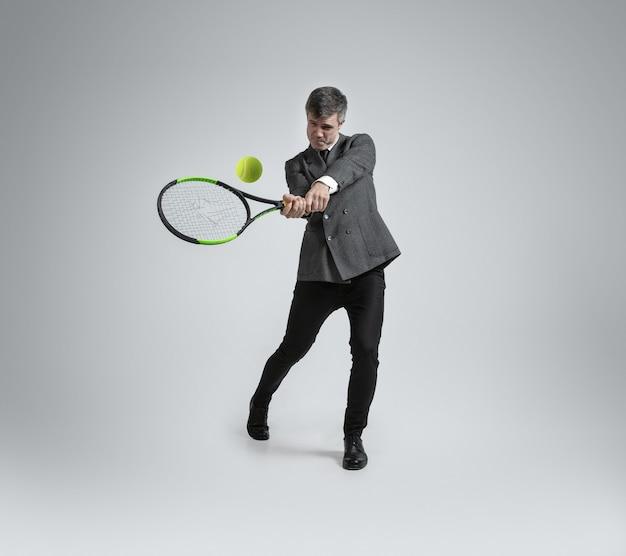 Homem caucasiano com roupa de escritório joga tênis isolado na parede cinza