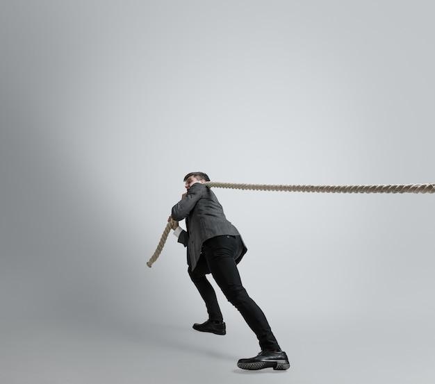Homem caucasiano com roupa de escritório treinando isolado na parede cinza