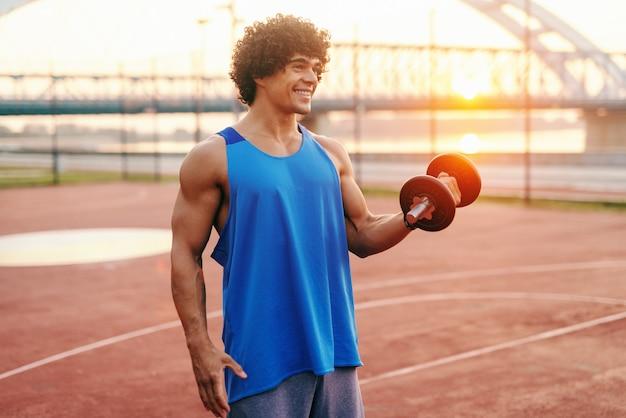 Homem caucasiano com sorriso e cabelo encaracolado, vestido com sportswear levantando halteres em pé na quadra de manhã.