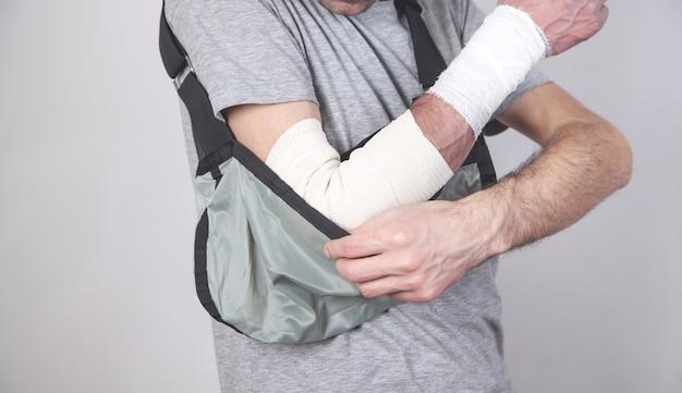 Homem caucasiano com tipóia de braço.