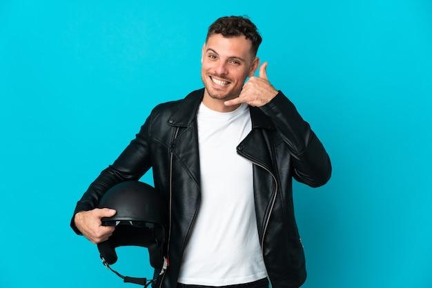 Homem caucasiano com um capacete de motocicleta isolado na parede azul, fazendo gesto de telefone. ligue-me de volta sinal