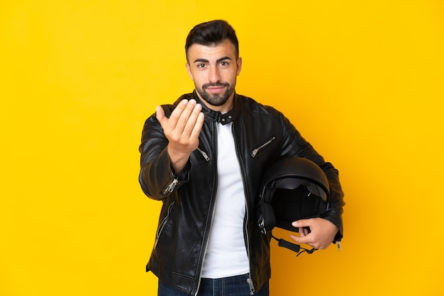 Homem caucasiano com um capacete de motocicleta sobre a parede amarela isolada, convidando a vir com a mão. feliz que você veio