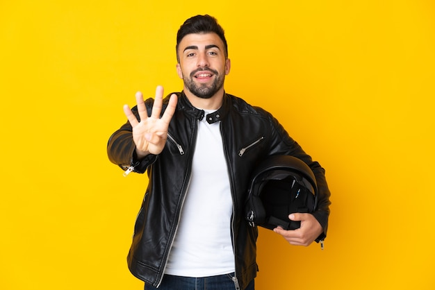 Homem caucasiano com um capacete de motocicleta sobre amarelo feliz e contando quatro com os dedos