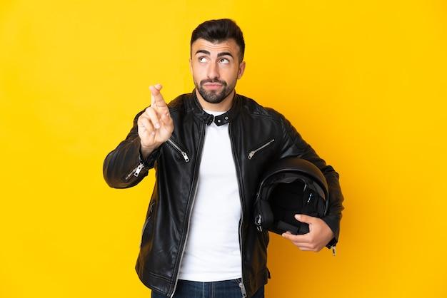 Homem caucasiano com um capacete de motociclista isolado em amarelo com os dedos se cruzando e desejando o melhor