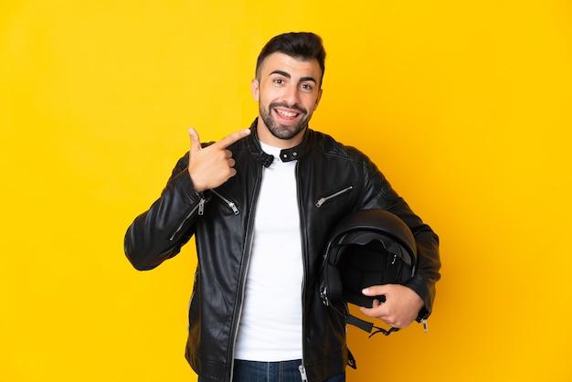 Homem caucasiano com um capacete de motociclista sobre amarelo fazendo um gesto de polegar para cima